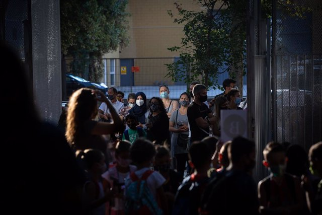 Pares i alumnes esperen les portes d'un col·legi durant el primer dia del curs escolar 2020-2021, a Barcelona, Catalunya (Espanya), a 14 de setembre del 2020.