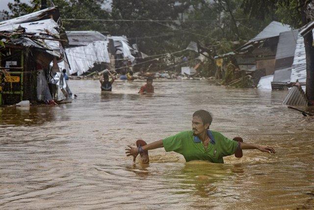 Un hombre camina hundido hasta los hombros debido a una inundación causada por el huracán 'Vamco'