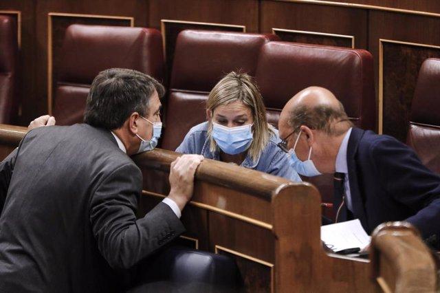 El portavoz del PNV en el Congreso de los Diputados, Aitor Esteban, habla con sus compañeros de grupo, Idoia Sagastizabal y Mikel Legarda, en una sesión plenaria