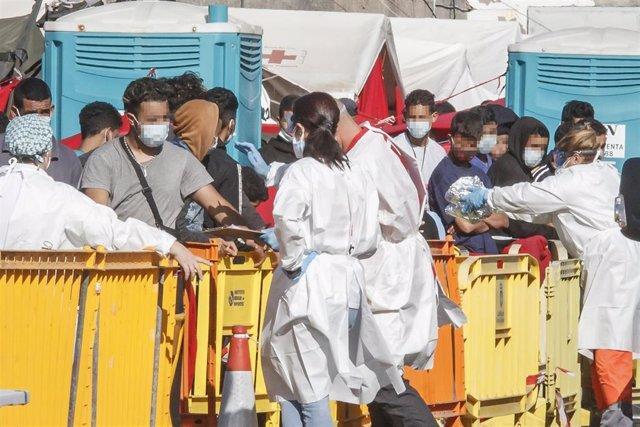 Varios inmigrantes son atendidos por personal sanitario en el Muelle de Arguineguín, en Gran Canaria,