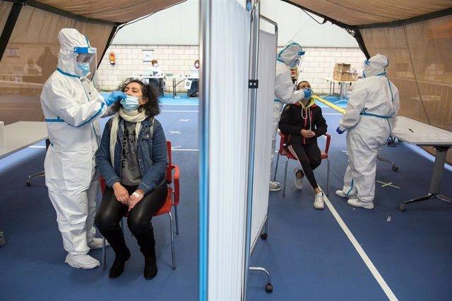 Varios trabajadores sanitarios totalmente protegidos realizan un test de antígenos de Covid-19 a dos vecinos el Complejo Deportivo El Plantío, en Burgos.