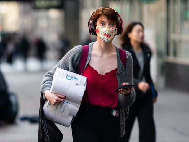 A woman wearing a protective mask carries a toilet paper package on the street on March 13, 2020 in New York City. President Donald Trump is expected to declare national emergency over coronavirus crisis today.