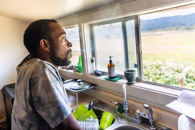 Hombre mirando por una ventana pensativo.