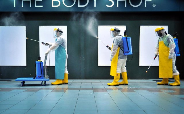22 November 2020, Malaysia, Labuan: Members of the Emergency Response Team (ERT) conduct a disinfection process at the Labuan Financial Park Complex after several workers had tested positive for coronavirus (COVID-19). Photo: Muqtadir Halim/BERNAMA/dpa