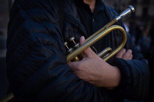 Un home sosté una trompeta en una concentració contra les restriccions.