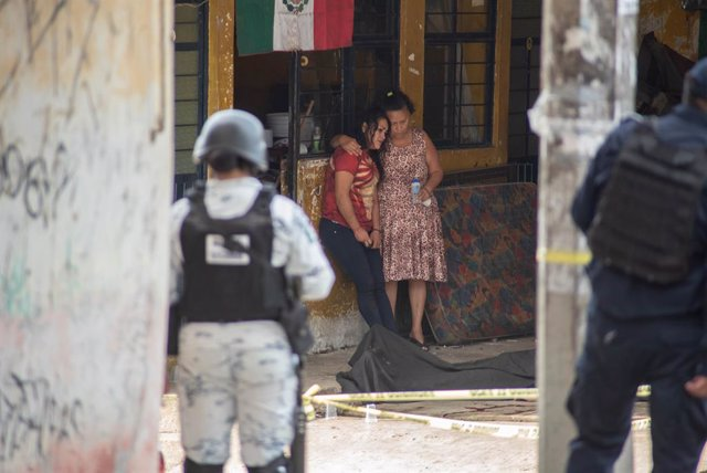 Dos mujeres junto al cadáver de un hombre abatido en Veracruz, México