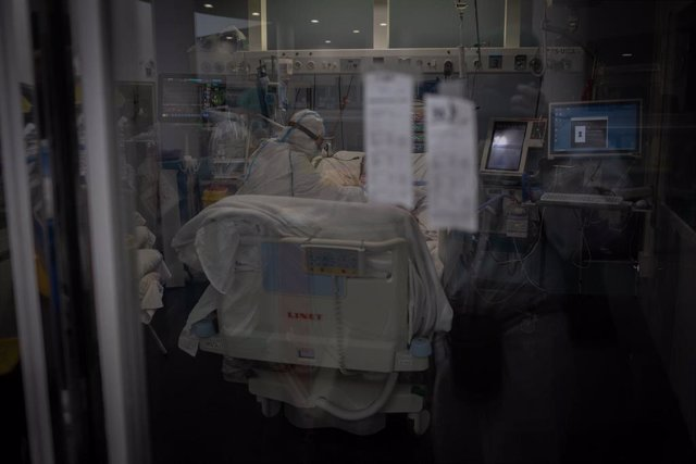 Trabajadores sanitarios protegidos atienden a un paciente en la Unidad de Cuidados Intensivos.