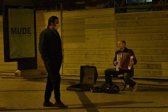 Hombre con mascarilla pasea junto a un acordeonista en Lisboa, Portugal