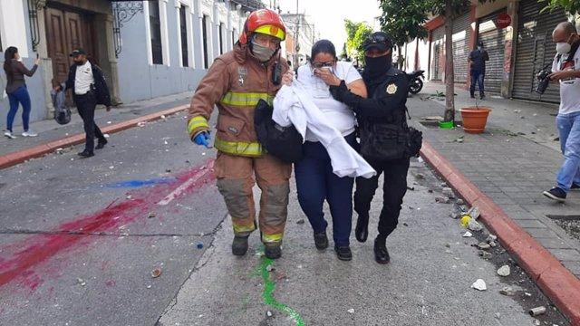 Una mujer afectada por el gas lacrimógeno y un policía durante las protestas contra el presidente Alejandro Giammattei en Guatemala