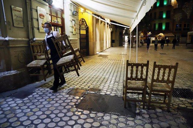 Un camarero se afanan en recogen la terraza del bar ubicado en el centro de la capital