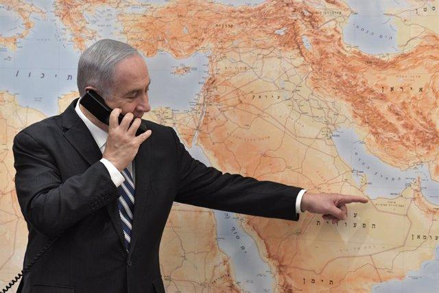 El primer ministro israelí, Benjamin Netanyahu, hablando por teléfono y señalando al golfo Pérsico en un mapa de Oriente Próximo