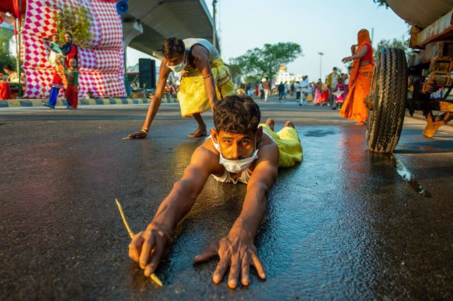 20 November 2020, India, Ghaziabad: A devotee lying on a road drags himself to the Hindon river as a ritual during the Chhath Puja celebration. Photo: Pradeep Gaur/SOPA Images via ZUMA Wire/dpa