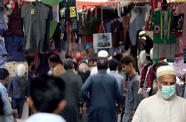Personas con mascarilla en un mercado de Karachi