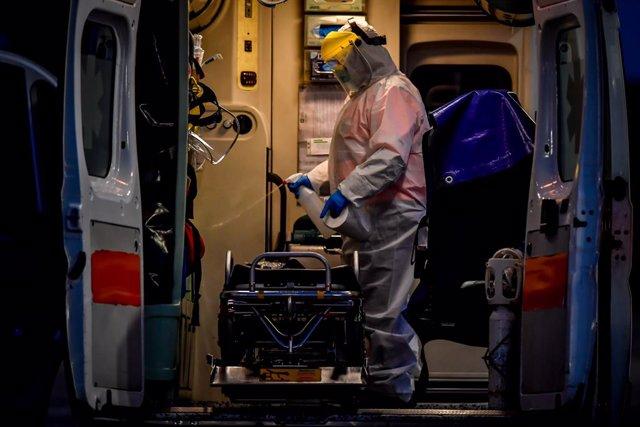 Un trabajador desinfecta una ambulancia en una campaña de test de coronavirus en Milán