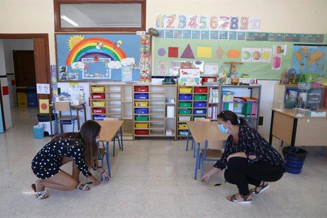 Dos profesoras de un colegio miden la distancia entre bancas en el aula infantil como medidas preventivas ante el COVID-19