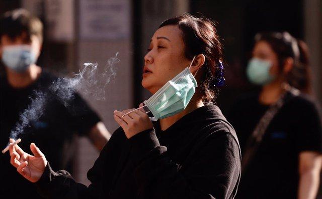 Una mujer se retira la mascarilla para fumar en Hong Kong.