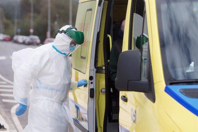 Un trabajador sanitario totalmente protegido cierra la puerta de una ambulancia tras recoger a un anciano de la residencia de ancianos de San Cibrao.