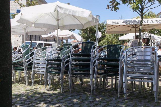 Mesas y sillas de terrazas recogidas en una terraza. Foto de archivo.