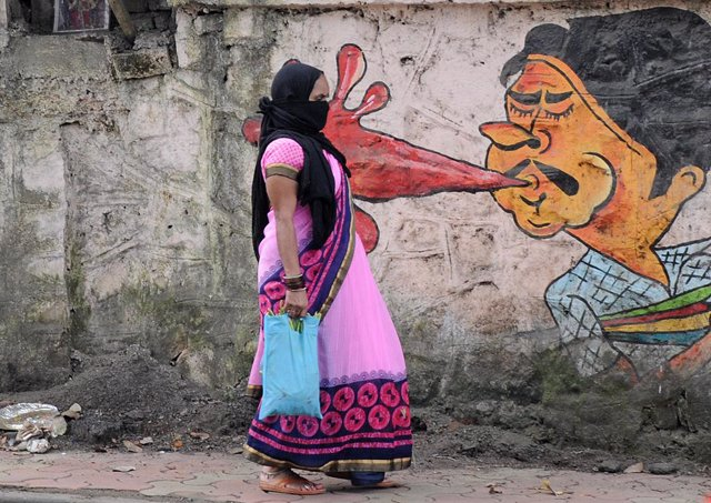 11 October 2020, India, Mumbai: A woman walks past a graffiti on a wall to create awareness about the dangers of spitting in public places amid the outbreak of coronavirus pandemic. Photo: Ashish Vaishnav/SOPA Images via ZUMA Wire/dpa