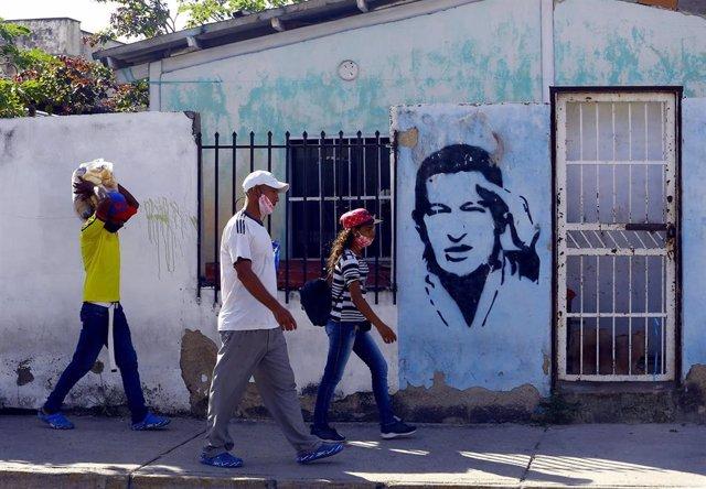 Personas con mascarillas ante un mural de Hugo Chávez en Carabobo