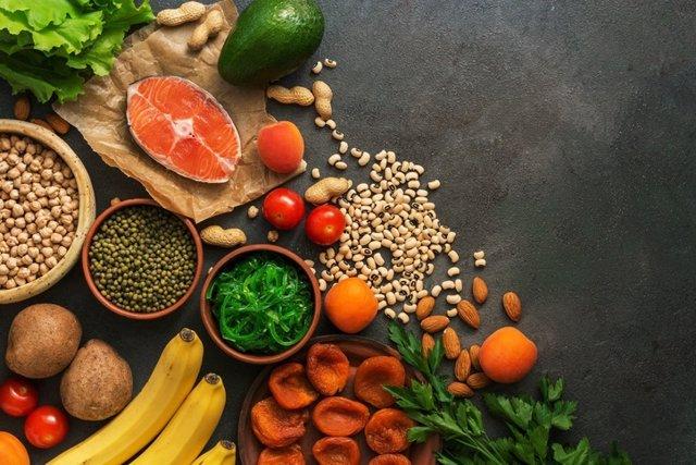 Alimentos saludables con alto contenido de potasio. Una variedad de legumbres, salmón, frutas, verduras, albaricoques secos, chuka de algas y nueces sobre un fondo oscuro.