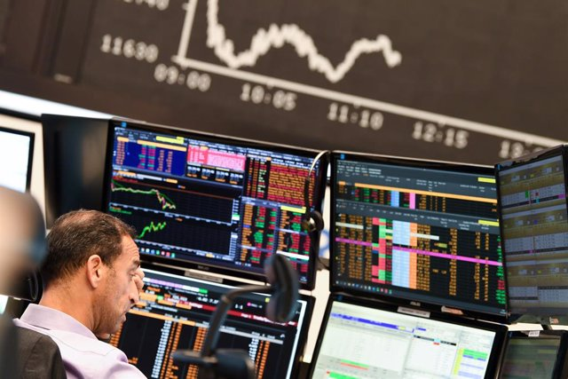 28 October 2020, Hessen, Frankfurt/Main: A stock trader observes his monitors on the floor of the Frankfurt Stock Exchange in front of the board with the falling Dax curve. Photo: Arne Dedert/dpa