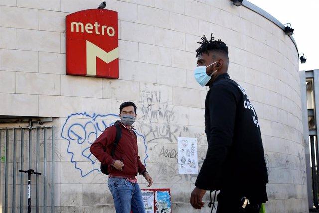 Personas con mascarilla junto a una parada del Metro de Lisboa