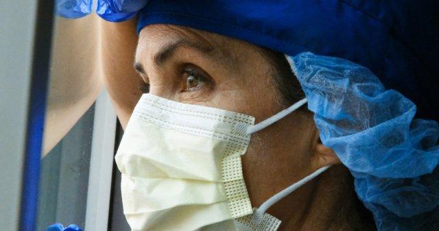 Foto recurs de doctora mirant per la finestra. Coronavirus. Covid-19.