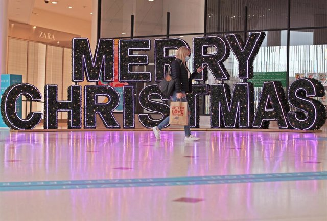 "24 November 2020, England, London: A woman walks past Christmassy decorated letters made of fir branches, which are installed in a shopping centre and form the words ""Merry Christmas"". Photo: Yui Mok/PA Wire/dpa"