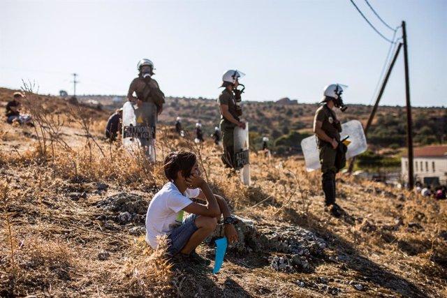 Un niño frente a la Policía de Grecia durante una protesta de migrantes que piden su reubicación después de que varios incendios destruyeran el campamento de Moria, en la isla de Lesbos