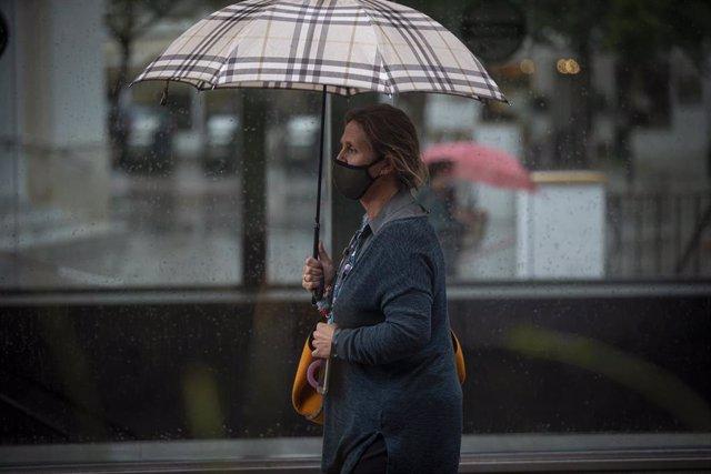Una mujer se protege bajo su paraguas durante una jornada de lluvia