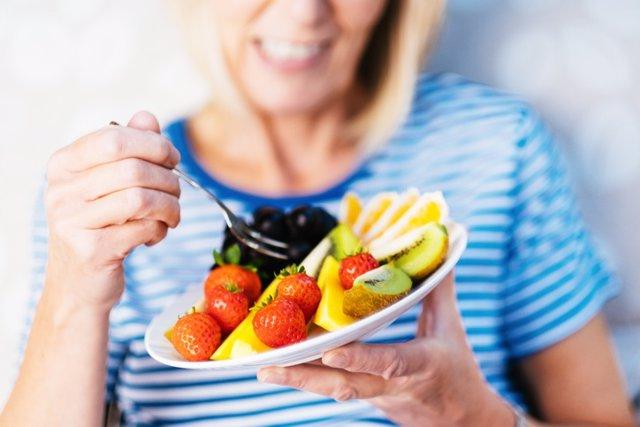 Fruta, macedonia de frutas, mujer comiendo fruta.