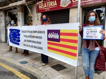 Un grupo de funcionarios interinos recibe con una pancarta de protesta a la comitiva española de la cumbre con Italia