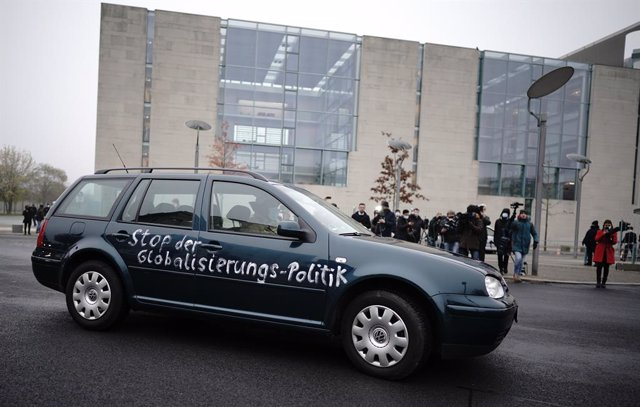 25 November 2020, Berlin: A fireman at the wheel removes a car, which crashed stands in the gate of the Federal Chancellery, with inscription on the door : Stop the policy of globalization. Photo: Michael Kappeler/dpa