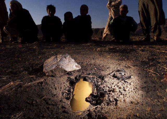 Unos niños se agolpan junto a una munición de racimo sin explotar en Afganistán (Imagen de Archivo)