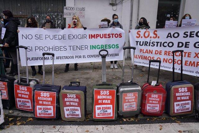Trabajadores de agencias de viaje colocan maletas como signo de protesta en una manifestación por la situación del sector convocada por la Asociación Plataforma en Defensa polas Axencias de Viaxe de Galicia frente al Parlamento gallego, en Santiago de Com