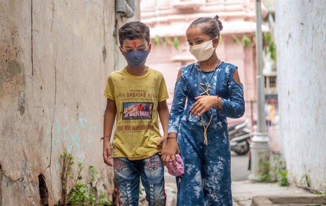 Dos niños con mascarilla en India.
