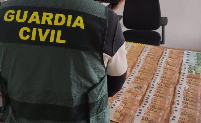 Un agente de la Guardia Civil junto al botín recuperado.
