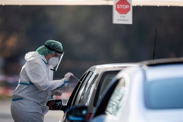 25 November 2020, Baden-Wuerttemberg, Nuertingen: An employee at a drive-thru testing centre takes a swab from a car driver for a coronavirus test. Photo: Tom Weller/dpa