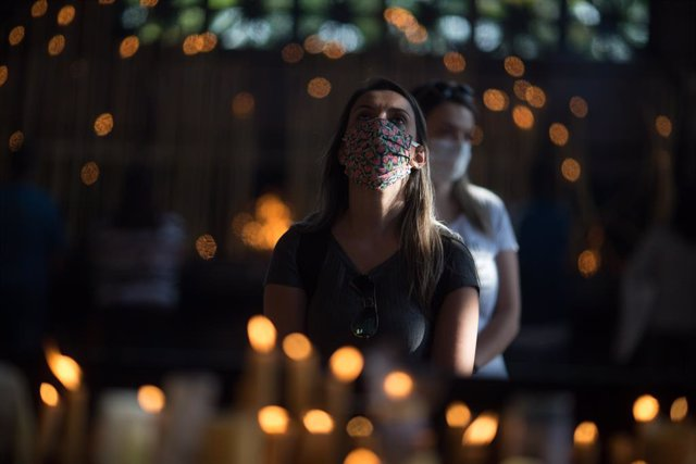 12 October 2020, Brazil, Aparecida: A woman prays in the candle room of Our Lady of Aparecida Basilica, on the feast day of Nossa Senhora Aparecida, the patron saint of Brazil. The feast masses had to be celebrated by small number of people due to the Cor