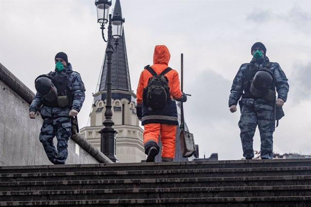 Dos oficiales de la Guardia Nacional rusa con mascarilla patrullando por el centro de Moscú