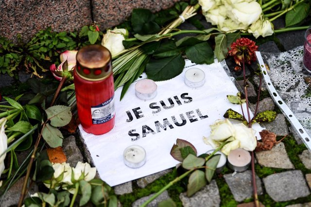 "27 October 2020, Berlin: A sign reading ""I am Samuel Paty' is seen among flowers and candles placed in front of the French embassy in Berlin. French teacher Samuel Paty was beheaded in a suburb outside Paris earlier this month for showing cartoons of Isla"