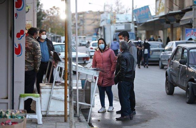 Personas con mascarillas en un mercado de Mashhad, Irán