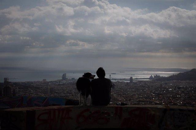 Un joven mira el paisaje en el mirador Turó de la Rovira, en Barcelona, Catalunya (España), a 16 de noviembre de 2020. El turismo internacional se desplomó este verano debido como consecuencia del coronavirus. Además, el pasado 15 de octubre el Govern de