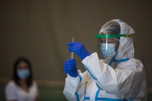 Una sanitaria atiende a una mujer durante las pruebas de cribado de covid-19 con test de antígenos en pabellones deportivos de la ciudad. En Sevilla (Andalucía, España), a 28 de octubre de 2020.