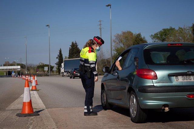Una agent dels Mossos d'Esquadra en un control demana a un conductor el justificant per sortir del seu municipi. Barcelona, Catalunya(Espanya), 9 d'abril del 2020.