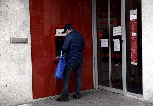 Un hombre saca dinero de un cajero del Banco Santander