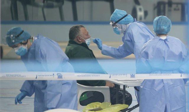 Un trabajador del SERMAS realiza un test de antígeno a un paciente en el Centro Deportivo Municipal Félix Rubio ubicado en Los Rosales, Villaverde, Madrid, (España), a 16 de octubre de 2020.