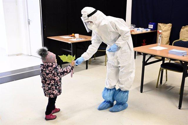 21 November 2020, Slovakia, Puchov: A child hands a Luau leaf to a healthcare worker at a coronavirus testing centre. Photo: Radovan Stoklasa/TASR/dpa