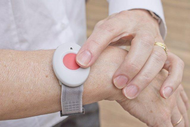 Una persona pulsa el botón de teleasistencia.